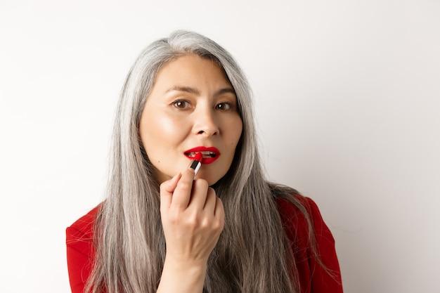 아름다움과 메이크업 개념. 회색 머리를 가진 세련 된 아시아 성숙한여 인, 거울을보고 흰색 배경 위에 서있는 빨간 립스틱을 적용합니다.