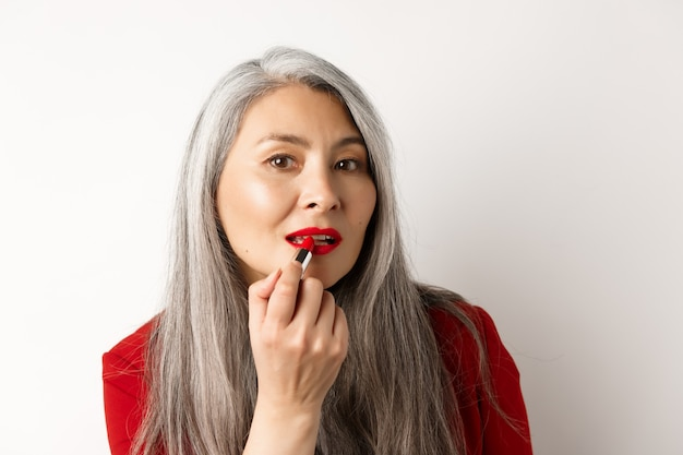 Концепция красоты и макияжа. стильная азиатская зрелая женщина с седыми волосами смотрит в зеркало и наносит красную помаду, стоя на белом фоне