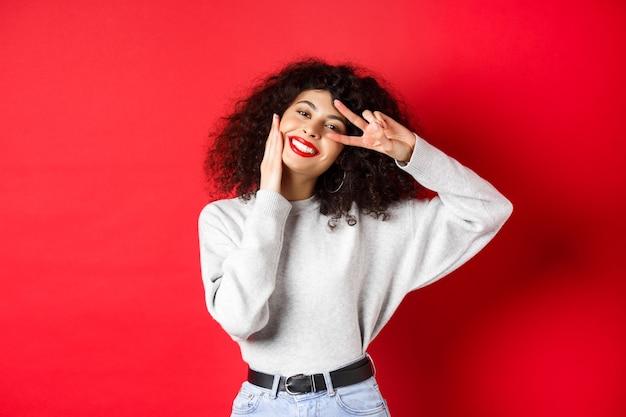 아름다움과 메이크업. 곱슬머리를 한 행복한 젊은 여성, 얼굴을 만지고 귀여운 미소로 v자 표시를 하고 빨간색 배경에 서 있습니다.