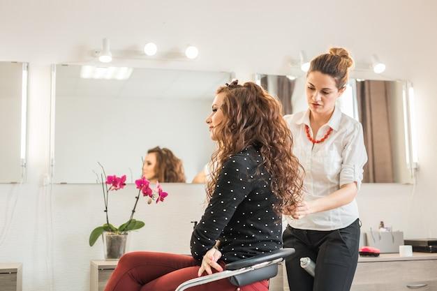 미용실에서 미용사와 함께 아름다움과 사람들의 개념 행복한 젊은 여성