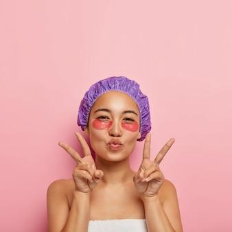 아름다움과 회춘 개념. 예쁜 한국 여성이 평화의 손짓을하고, 입술을 접고, 얼굴에 눈 패치를하고, 보라색 목욕 모자를 쓰고, 샤워 후 스파 절차를 즐깁니다.