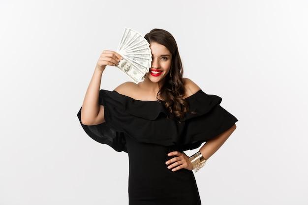 아름다움과 쇼핑 개념. 달러를 표시 하 고 웃 고, 돈으로 흰색 배경 위에 서있는 붉은 입술을 가진 유행 여자.