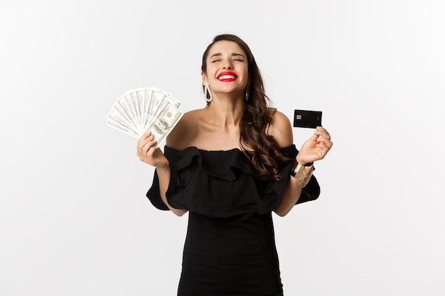 美容とショッピングのコンセプト。スタイリッシュなドレスを着て、満足そうに見える、クレジットカードとお金を持って、白い背景の上に立って満足している若い女性。