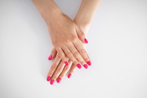 아름다움과 피부 관리 개념. 젊은 여자와 흰색 배경에 아름 다운 매니큐어, 평면 누워의 아름 다운 손.
