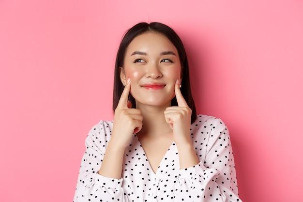 아름다움과 피부 관리 개념. 아름 다운 아시아 여자의 근접 뺨을 파고 웃 고 만족, 분홍색 배경 위에 서 서