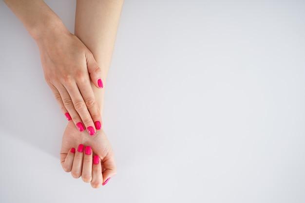 텍스트, 평면 누워 공간 아름다움과 피부 관리 개념. 아름 다운 여성의 손과 흰색 바탕에 아름 다운 매니큐어.