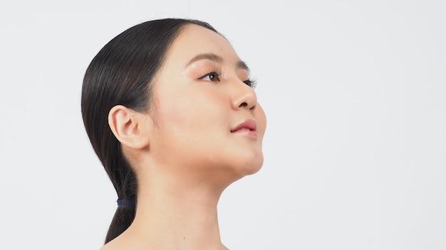 美しさと肌のコンセプト。若いアジアの女性の美しさの顔は、スキンケア化粧品を補い、自然な健康を柔らかく、しっかりと年齢を超えた顔の肌に見せます。