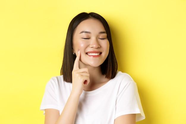 美容とスキンケア。短い黒髪、健康な輝く肌、笑顔で頬のくぼみに触れ、黄色の上に立っている若いアジアの女性のクローズアップ。