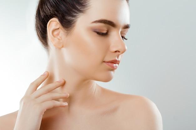 아름다움과 스파 개념. 깨끗하고 신선한 피부를 가진 아름 다운 젊은 여자는 자신의 얼굴을 터치하고 smiling.facial 치료.