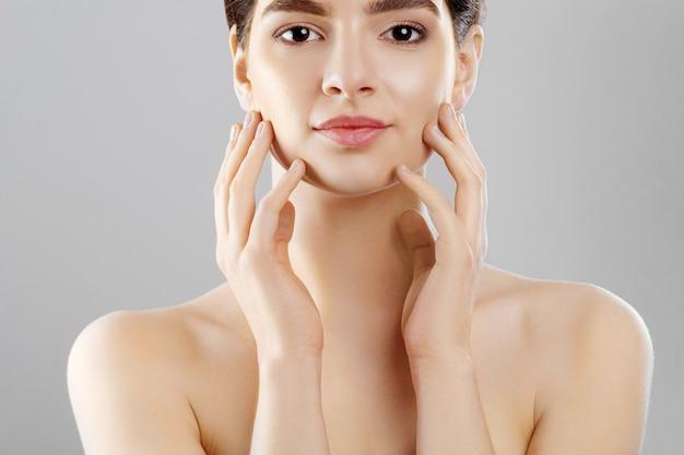 아름다움과 스파 개념. 깨끗하고 신선한 피부를 가진 아름 다운 젊은 여자는 자신의 face.facial 치료를 터치합니다.