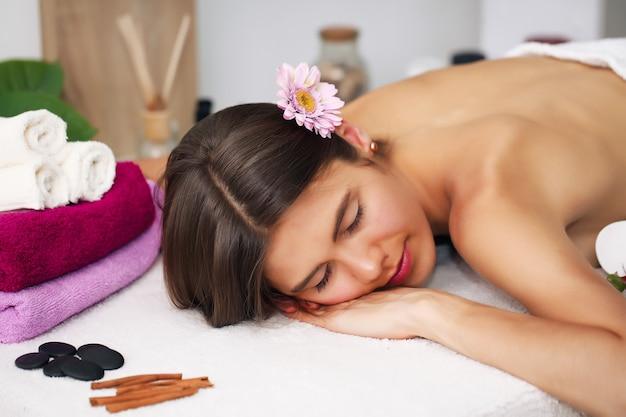 Концепция красоты и спа - счастливая женщина в спа-салоне, лежа на массажном столе