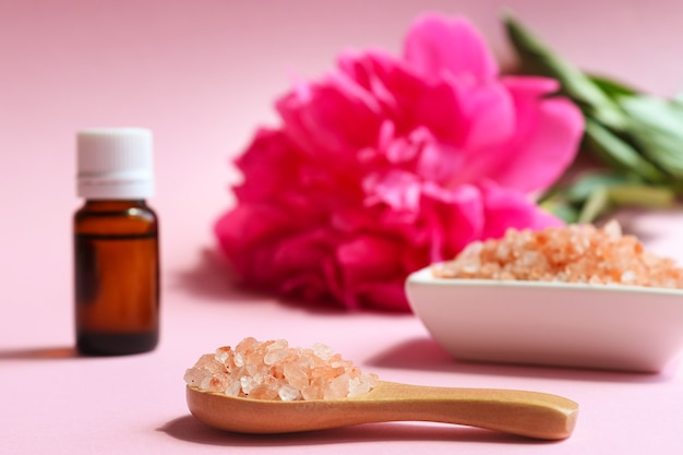 木のスプーンのエッセンシャルオイルと牡丹の花の選択的な焦点に美容とスパのコンセプトピンクヒマラヤ塩のクローズアップ