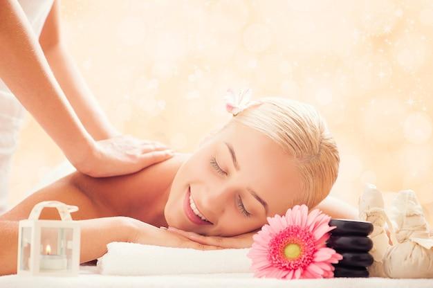 Концепция красоты и спа - женщина в спа-салоне, получающая массаж