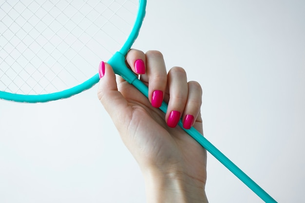 Концепция красоты и спорта. красивая женская рука держит ракетку для бадминтона на белом фоне. красивый маникюр.