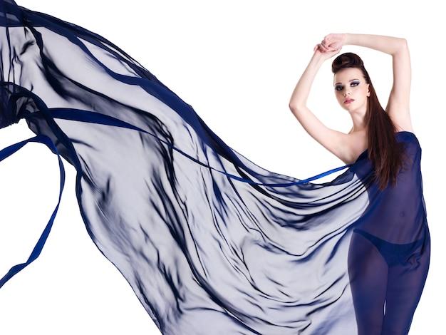 明るい青いシフォンでポーズをとる若い女性の美しさとスタイル-空白