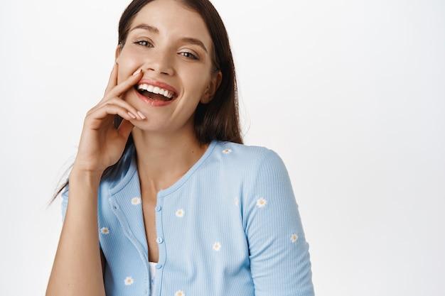 美しさと優しさ。幸せな率直な女性、笑って笑って、化粧なしで健康な完璧な肌に触れて、スキンケアの概念と白の美容