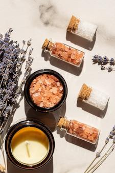 美しさとウェルネスのコンセプト-ガラス瓶の海塩と木製トレイのキャンドルと大理石の背景にラベンダーの束