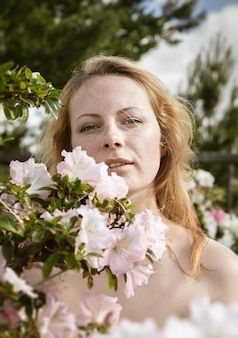 美しさと若さの概念。ツツジの花の中で美しい金髪の若い女性の肖像画