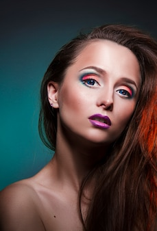 Beauty art makeup on the face of a woman girl with red hair