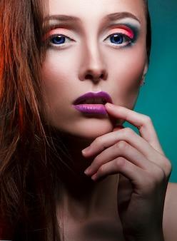 Косметика искусства красоты на лице девушки женщины с красными волосами. идеальная девушка с большими голубыми глазами на зеленом фоне. профессиональная косметика по уходу за кожей лица и тела