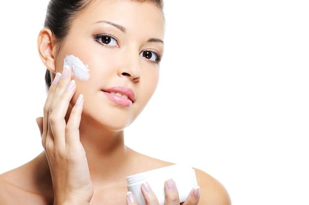 Bellezza femminile asiatica skincare del viso applicando crema cosmetica sulla sua guancia