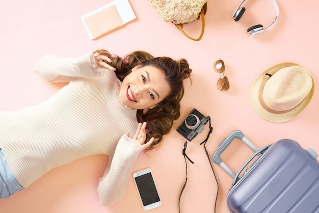Beauty asian girl lying on pink floor with all travel luggage around her.