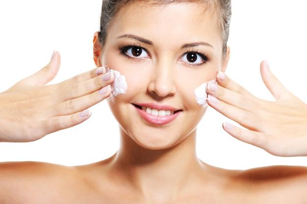 아름다움 아시아 웃는 젊은 성인 여자는 그녀의 얼굴에 화장품 크림을 적용