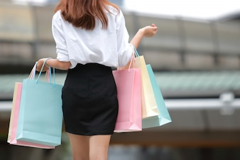 Beauty Asian woman holding colorful shopping bags.