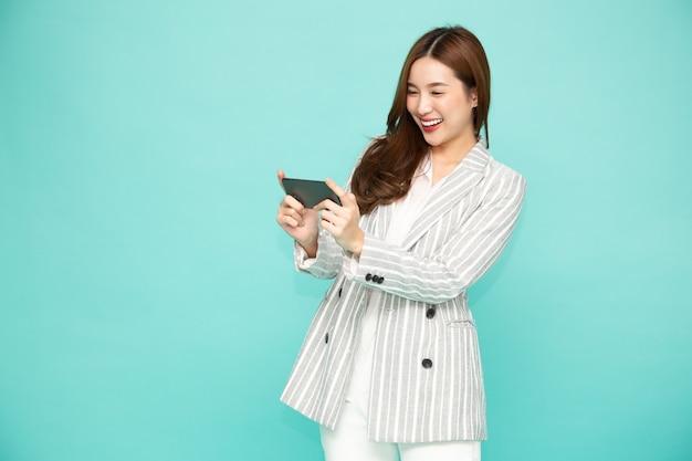 녹색 배경에 고립 된 스마트 폰으로 모바일 게임 응용 프로그램을 재생하는 아름다움 아시아 여자