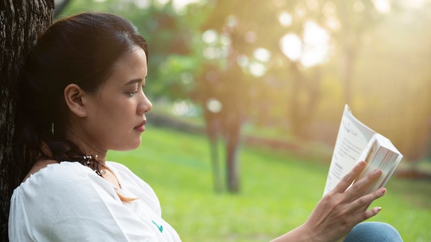 Beauty asian woman reading book at park on sunset.