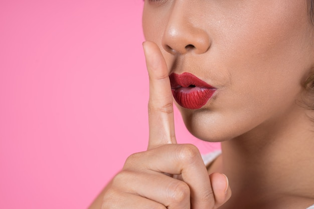 Beauty asian woman red lips and finger showing hush silence sign