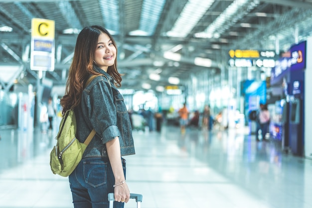 Beauty asian woman traveling and holding suitcase in the airport.
