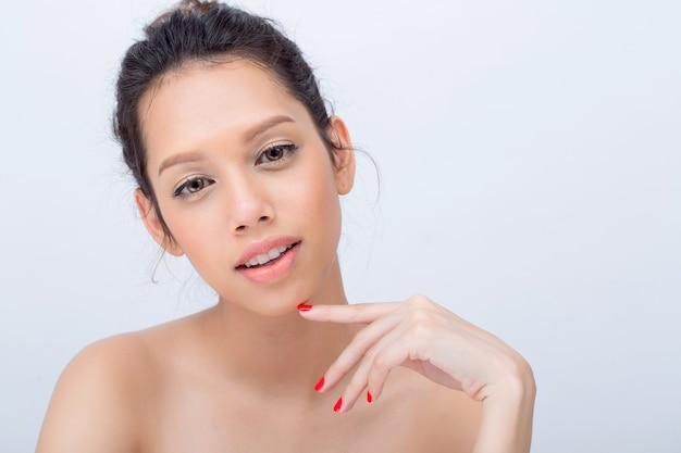 V字型の顔を持つ美容アジアの若い女性のファッションモデルは、コピースペース、スパのコンセプト、メイクアップ、スキンケア、ファッションの白い背景に自然なメイクアップ