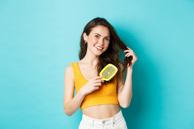 Beauty. attractive young woman brushing her hair with hairbrush and looking dreamy at top copy space, smiling, standing against blue background