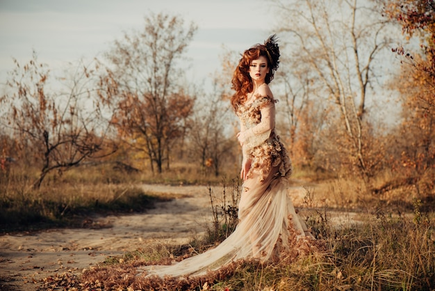 Beauty autumn woman in dress with leaves