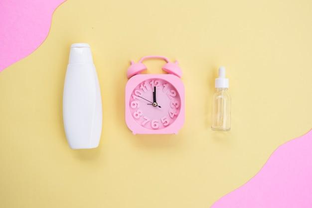 Предпосылка красоты косметических бутылок и будильника на желтой и розовой бумажной предпосылке. концепция ухода за кожей летом