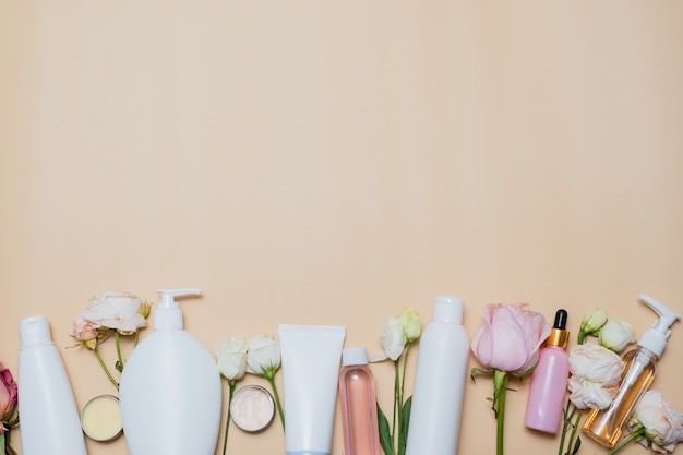Beauty background with facial cosmetic products and flowers on pastel beige desktop background.