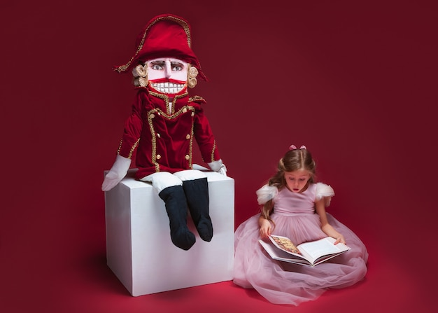 A beauty ballerina sitting near nutcracker and reading book at red studio