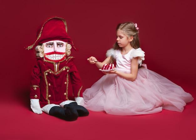 Un standig della ballerina di bellezza vicino alle schiaccianoci allo studio rosso