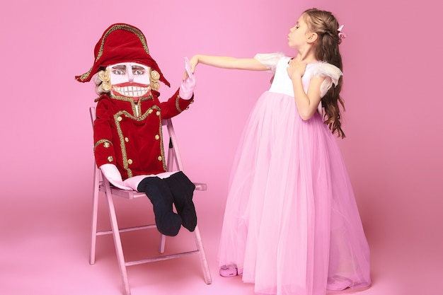 Beauty ballerina with nutcracker on pink