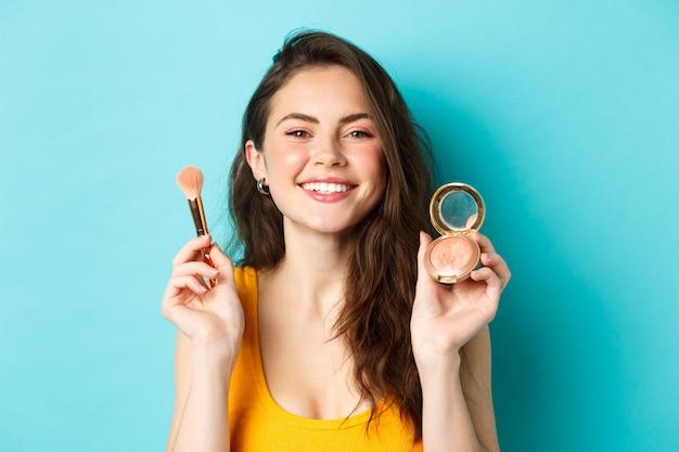 아름다움. 행복한 얼굴을 한 아름다운 여성 모델, 웃고 있고 얼굴이 붉어진 메이크업 브러쉬를 보여주며 파란색 배경 위에 서 있습니다.
