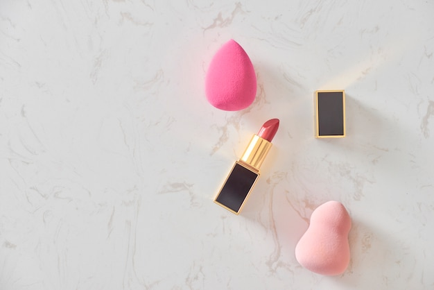 Beauty blenders and lipstick on a marble table