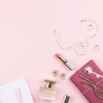 Beauty blog concept. accessories, flowers, cosmetics and jewelry on pink background, copyspace. womens day concept