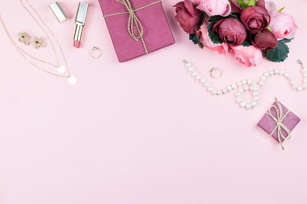 Концепция блога красоты. коллекция с аксессуарами, цветами, косметикой и украшениями на розовом фоне, copyspace. женский день концепция, вид сверху