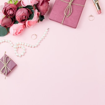 Beauty blog concept flat lay. fashion accessories, flowers, cosmetics, jewelry on pink background, copyspace.