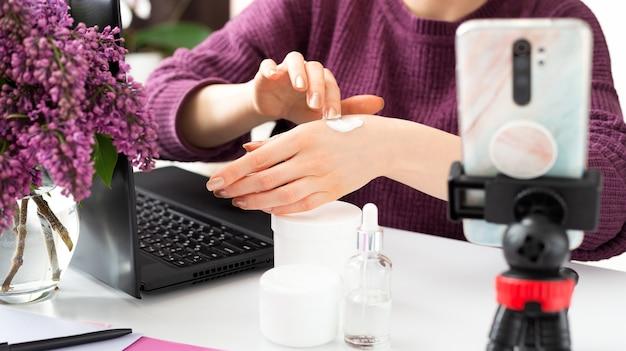 뷰티 블로거가 여성의 손에 크림을 바르십시오.