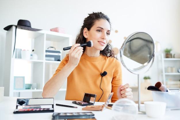 Бьюти-блогер наносит контурную пудру на лицо с помощью кисти для макияжа, горизонтальный снимок под низким углом
