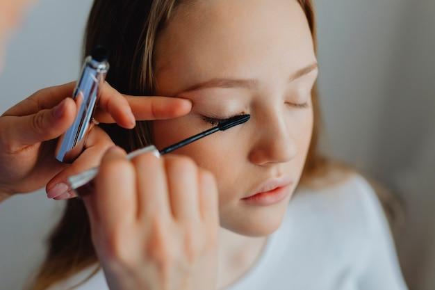그녀의 모델에 마스카라를 바르는 뷰티 블로거