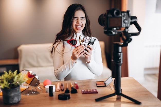 Бьюти-блогер-подражатель женщина снимает ежедневный учебник по макияжу на камеру. влиятельная молодая женщина в прямом эфире транслирует обзор косметики в домашней студии. работа влогера. солнцезащитные очки в руках.