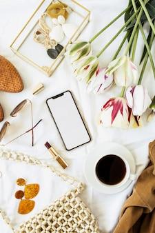 美容ブロガーのホームオフィスデスク。空白の画面のスマートフォン、チューリップの花の花束、白いリネンの服やアクセサリー。フラットレイ
